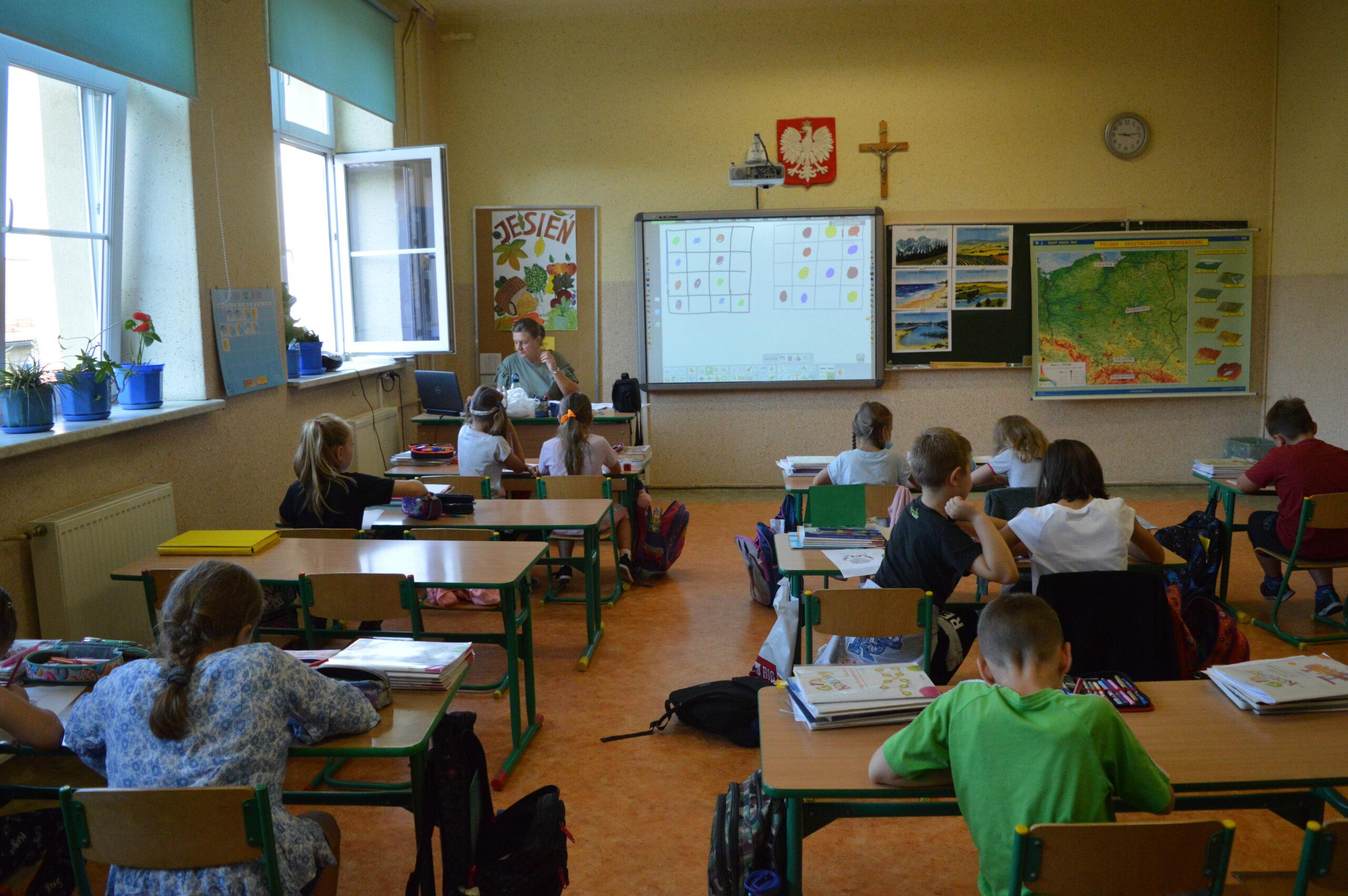 grupa uczniów w klasie z nauczycielem