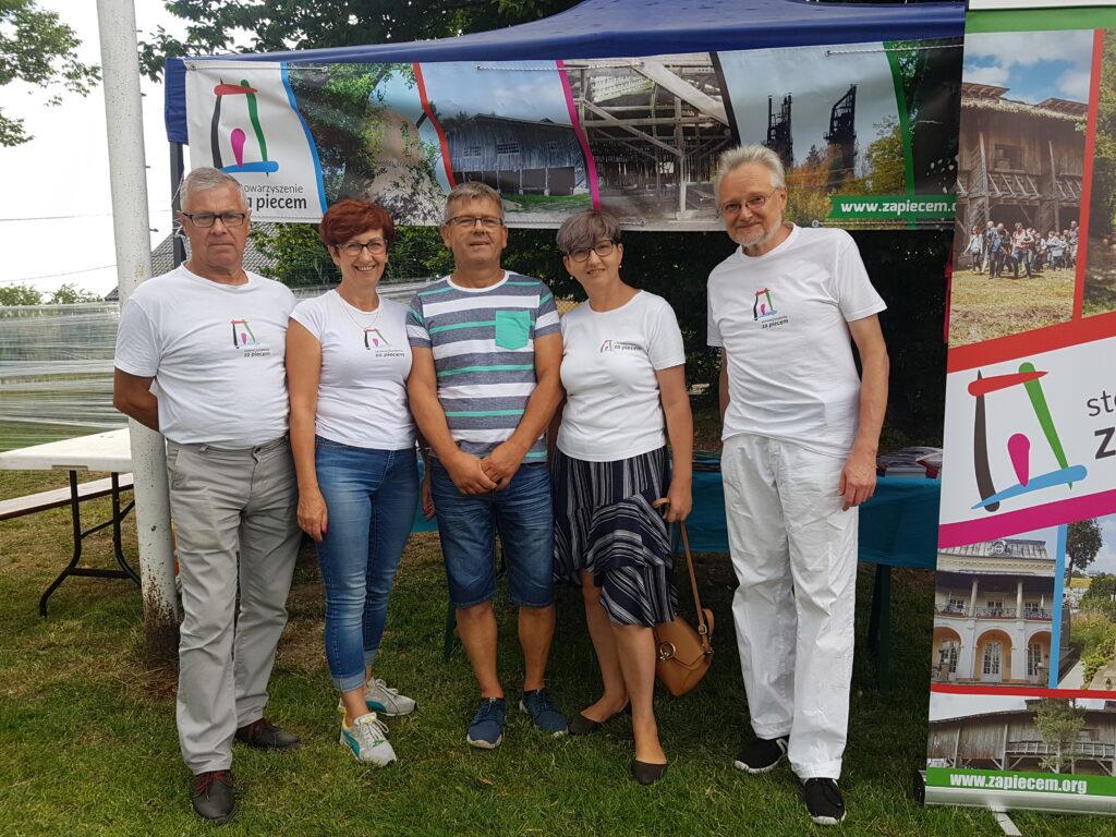 Fotografia pięciu osób, które stoją przed namiotem wystawowym. Na fotografii członkowie Stowarzyszenia Za Piecem.